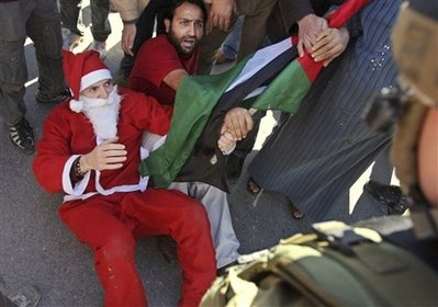Santa pushed to the groud during nonviolent action in Ma'sara south of Bethlehem