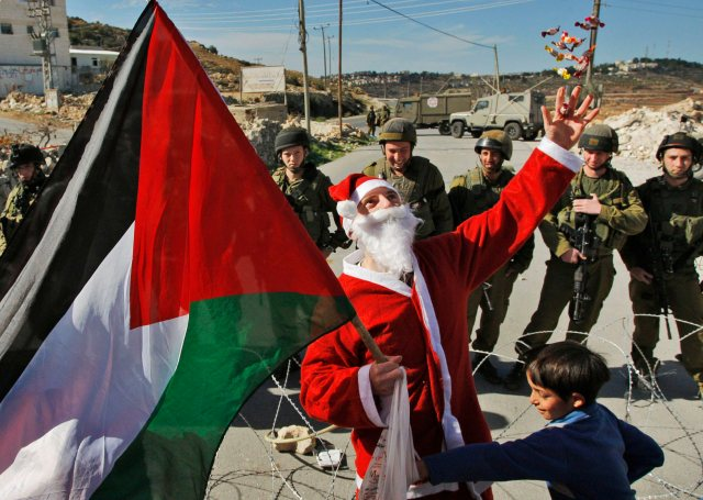 Santa Clause in the village of Masara handing candy to the children south of Bethlehem